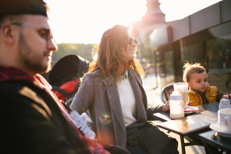 Ευτυχής νέα οικογένεια στον καφέ υπαίθρια την ηλιόλουστη ημέρα στοκ εικόνα με δικαίωμα ελεύθερης χρήσης