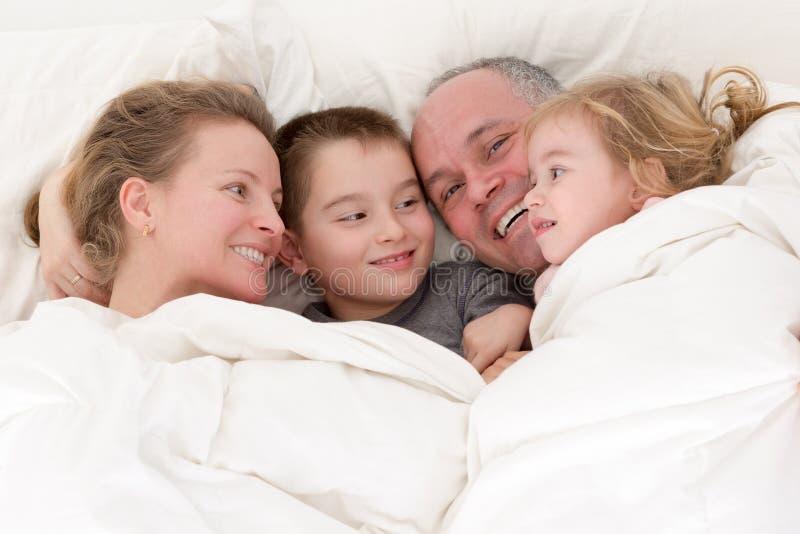 Ευτυχής νέα οικογενειακή αγκαλιά μαζί στο κρεβάτι στοκ εικόνα με δικαίωμα ελεύθερης χρήσης