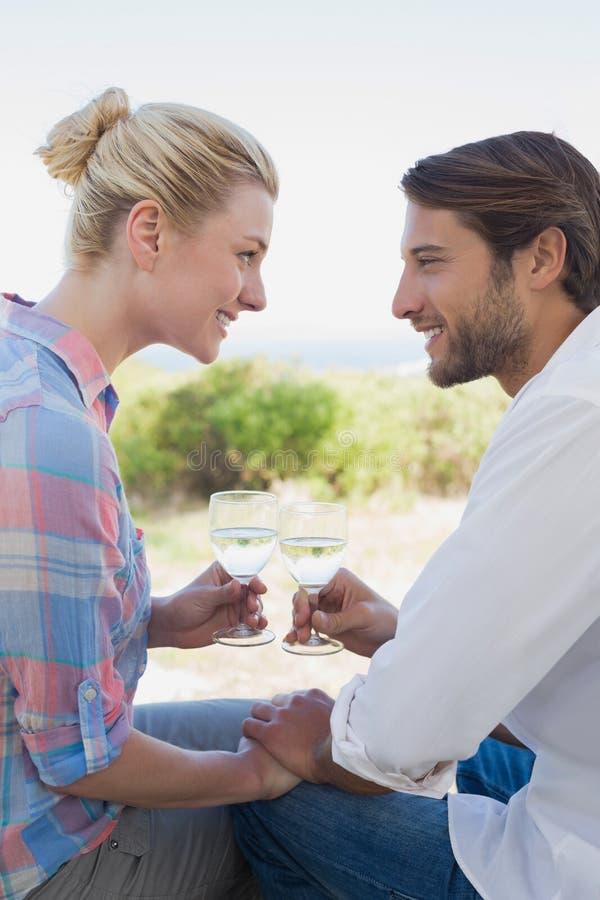 Ευτυχής νέα συνεδρίαση ζευγών στον κήπο που απολαμβάνει το κρασί από κοινού στοκ εικόνες με δικαίωμα ελεύθερης χρήσης