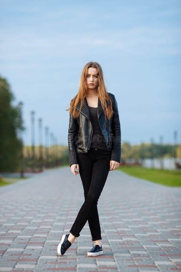 Ευτυχής νέα όμορφη γυναίκα στα μαύρα μαύρα τζιν σακακιών δέρματος ολίσθηση-στην τοποθέτηση για τις πρότυπες δοκιμές στο θερινό πά στοκ φωτογραφία με δικαίωμα ελεύθερης χρήσης