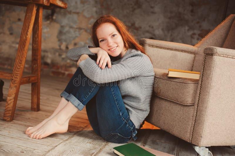 Ευτυχής νέα redhead γυναίκα που χαλαρώνει στο σπίτι και που διαβάζει τα βιβλία στοκ φωτογραφία