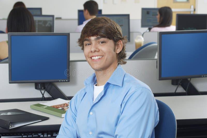 Ευτυχής νέος άνδρας σπουδαστής στο εργαστήριο υπολογιστών στοκ εικόνα με δικαίωμα ελεύθερης χρήσης
