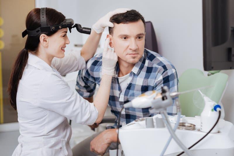 Ευτυχής νέος γιατρός που εξετάζει το αυτί του φίλου της στοκ φωτογραφία