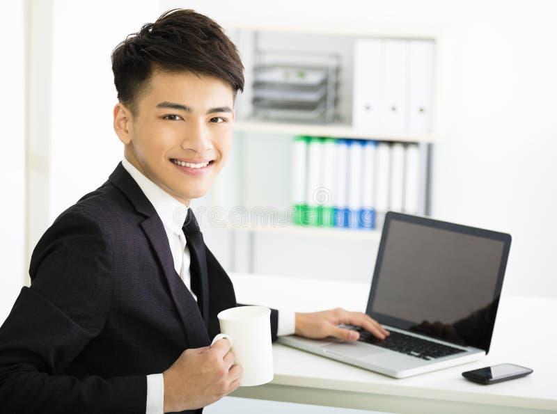 Ευτυχής νέος επιχειρηματίας με το lap-top στην αρχή στοκ φωτογραφίες