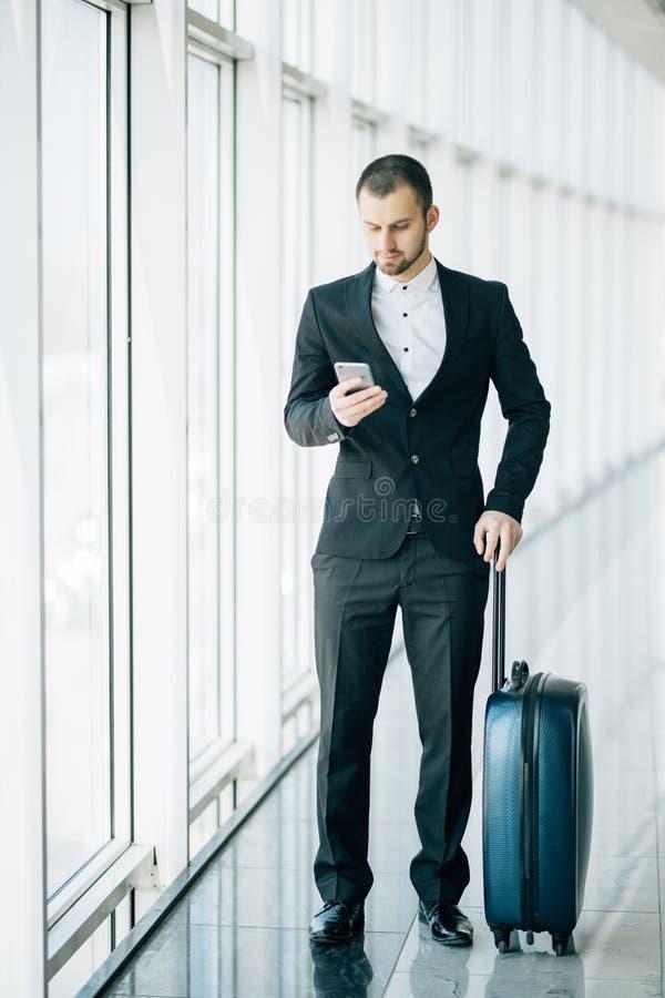 Ευτυχής νέος επιχειρηματίας που περπατά και που εξετάζει το κινητό τηλέφωνο στον αερολιμένα Όμορφο ανώτατων στελεχών επιχείρησης  στοκ εικόνες με δικαίωμα ελεύθερης χρήσης