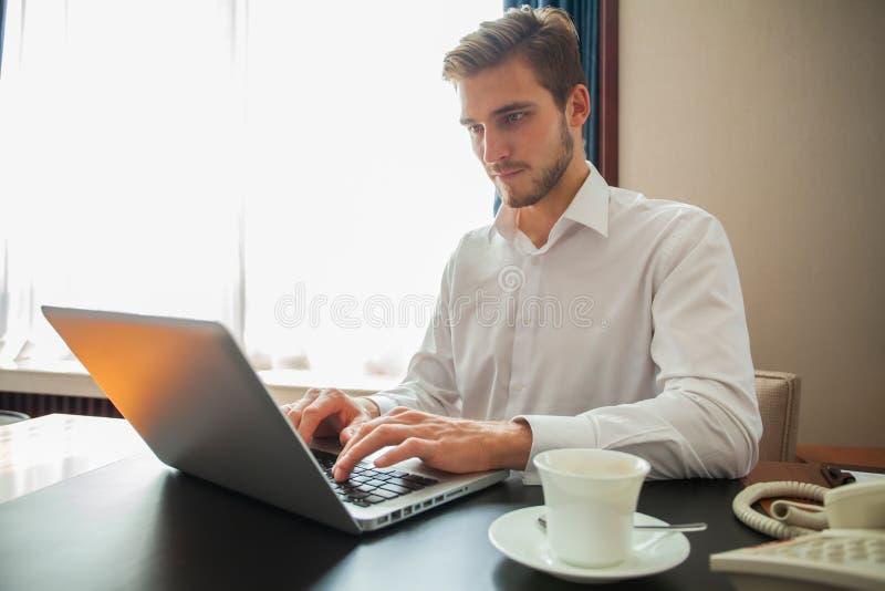 Ευτυχής νέος επιχειρηματίας που χρησιμοποιεί το lap-top στο γραφείο γραφείων του στοκ φωτογραφία με δικαίωμα ελεύθερης χρήσης