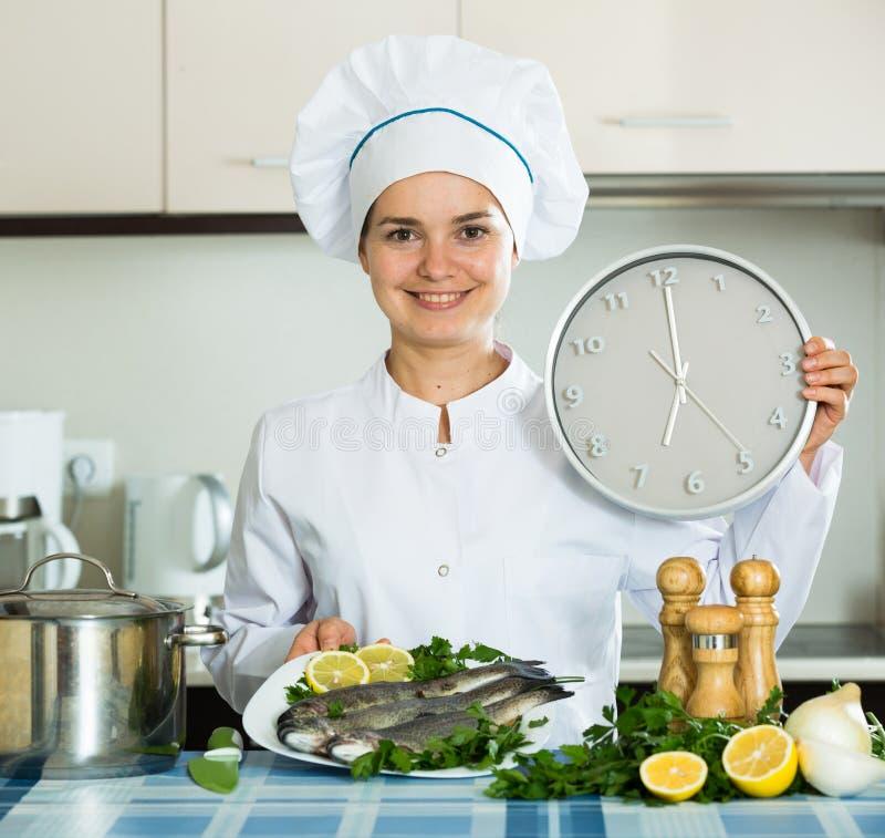Ευτυχής νέος μάγειρας που προετοιμάζει τα νόστιμα ψάρια για το γεύμα στοκ εικόνες