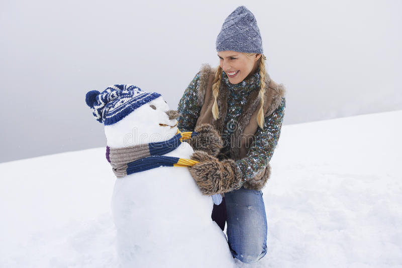 Ευτυχής νέος ντύνοντας χιονάνθρωπος γυναικών στοκ εικόνες