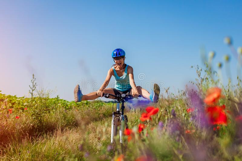 Ευτυχής νέος ποδηλάτης γυναικών που οδηγά ένα ποδήλατο βουνών στο θερινό τομέα Κορίτσι που έχει τα ανυψωτικά πόδια διασκέδασης στοκ φωτογραφία με δικαίωμα ελεύθερης χρήσης