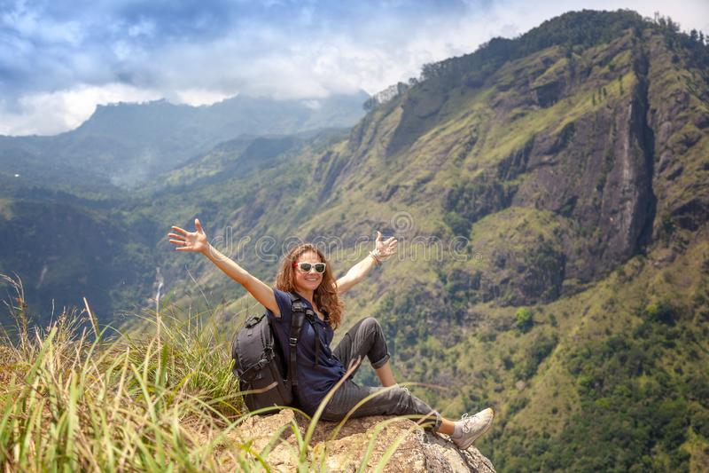 Ευτυχής νέος όμορφος τουρίστας κοριτσιών με ένα σακίδιο πλάτης Καθίστε στα βουνά και απολαύστε τη θέα και τη φύση στοκ φωτογραφία με δικαίωμα ελεύθερης χρήσης