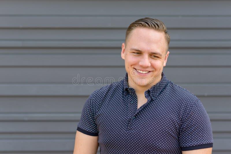 Ευτυχής νεαρός άνδρας με ένα γοητευτικό χαμόγελο στοκ φωτογραφία με δικαίωμα ελεύθερης χρήσης