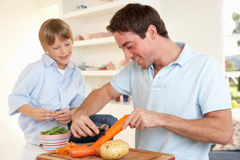 Ευτυχής νεαρός άνδρας με τα λαχανικά αποφλοίωσης αγοριών στοκ εικόνες