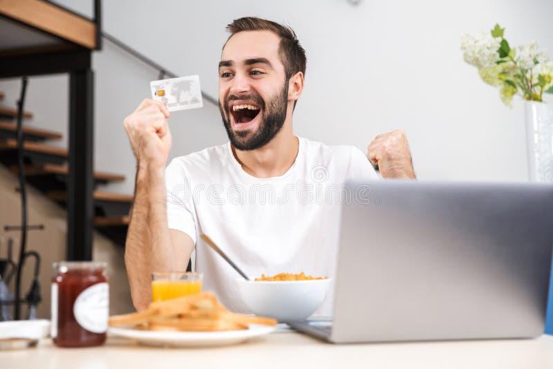 Ευτυχής νεαρός άνδρας που έχει το πρόγευμα στην κουζίνα στοκ εικόνες