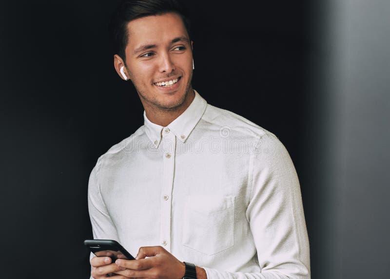 Ευτυχής νεαρός άνδρας που χαμογελά, texting μηνύματα από το κινητό τηλέφωνο του πέρα από το μαύρο υπόβαθρο στούντιο, με τα ασύρμα στοκ εικόνα