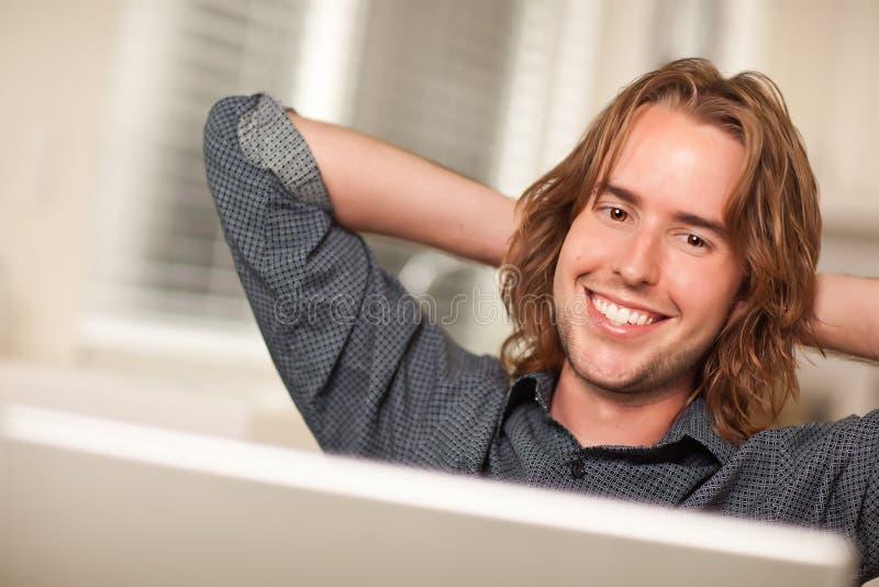 Ευτυχής νεαρός άνδρας που χρησιμοποιεί το φορητό προσωπικό υπολογιστή στοκ εικόνα