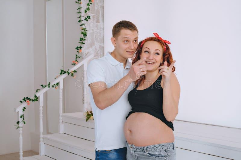 Ευτυχής νεαρός άνδρας και μια νέα όμορφη γυναίκα, που κοιτάζει στην πλευρά Σε αναμονή για το μωρό Έγκυος κοκκινομάλλης γυναίκα στοκ εικόνες