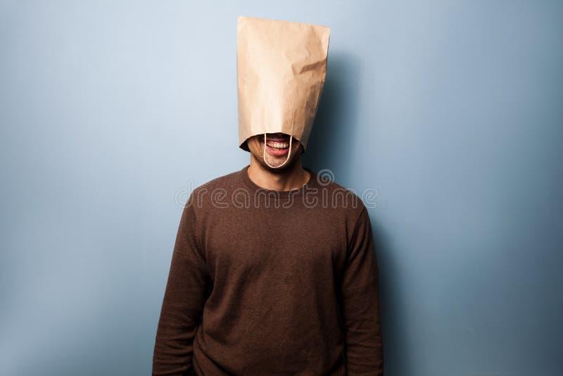 Ευτυχής νεαρός άνδρας με μια τσάντα πέρα από το κεφάλι του στοκ εικόνες