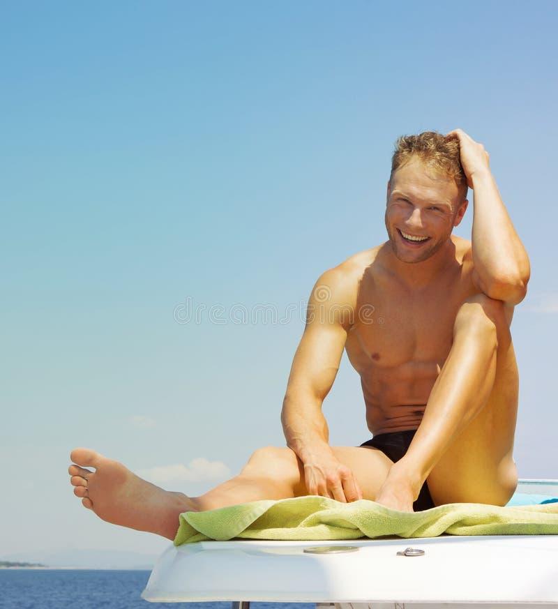 Ευτυχής νεαρός άνδρας με το κοστούμι λουσίματος σε μια βάρκα στοκ εικόνες