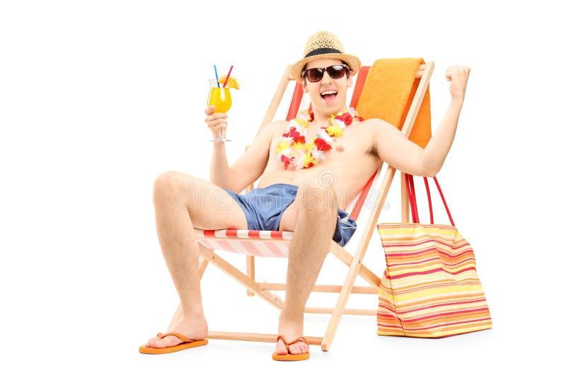 Ευτυχής νεαρός άνδρας που απολαμβάνει ένα κοκτέιλ και που κάθεται σε μια καρέκλα παραλιών στοκ εικόνα