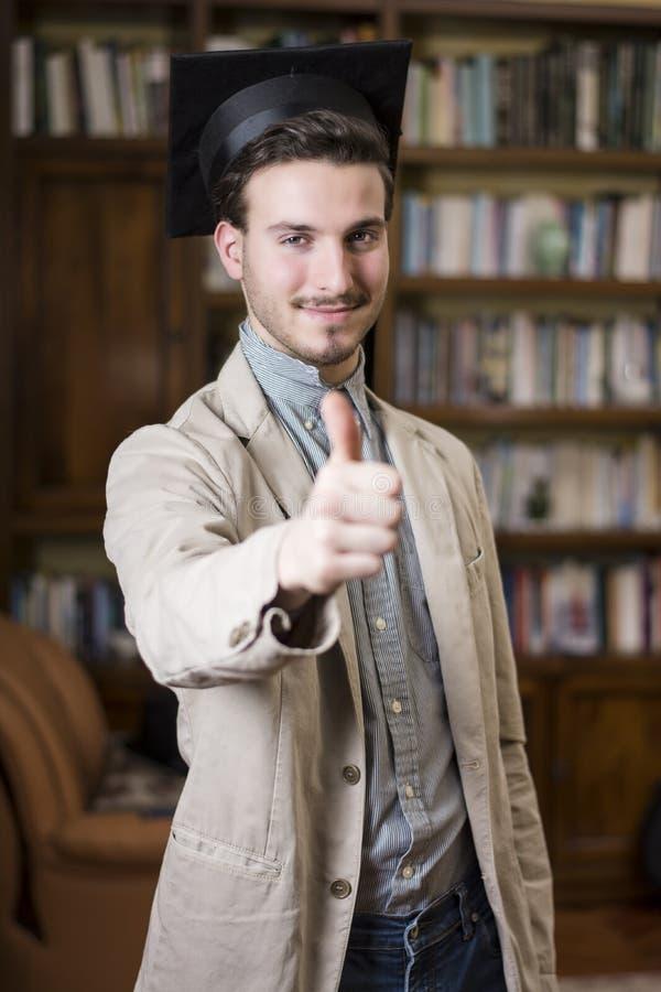 Ευτυχής νεαρός άνδρας που βαθμολογεί από το κολλέγιο, με το καπέλο βαθμολόγησης στοκ εικόνες