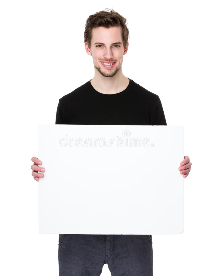 Ευτυχής νεαρός άνδρας που παρουσιάζει και που επιδεικνύει αφίσσα στοκ φωτογραφίες