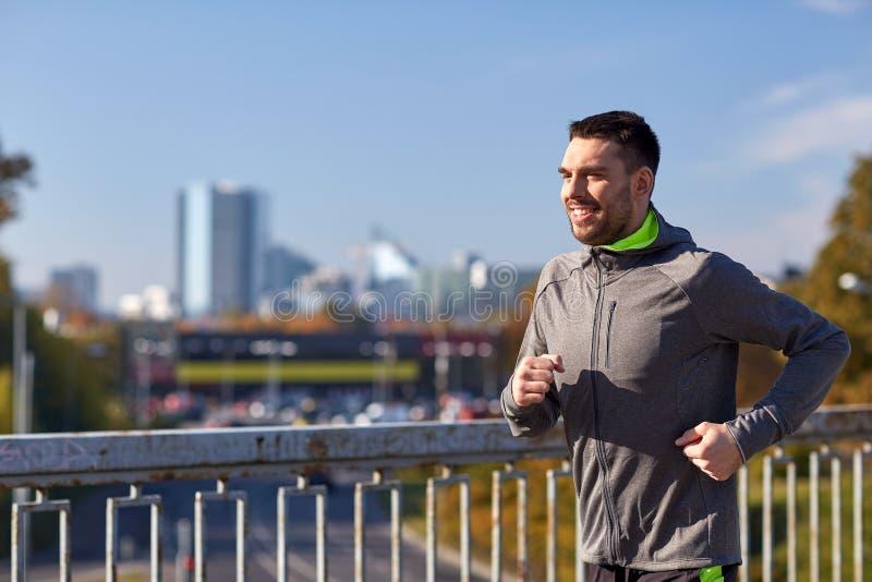 Ευτυχής νεαρός άνδρας που τρέχει πέρα από τη γέφυρα πόλεων στοκ φωτογραφία με δικαίωμα ελεύθερης χρήσης