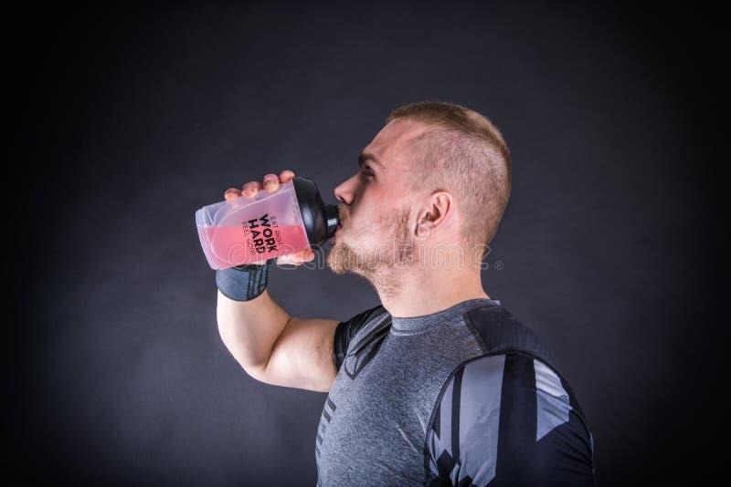 Ευτυχής νεαρός άνδρας sportswear στο ενεργειακό ποτό κατανάλωσης στη γυμναστική ενάντια στο σκοτεινό bacground στοκ φωτογραφία με δικαίωμα ελεύθερης χρήσης