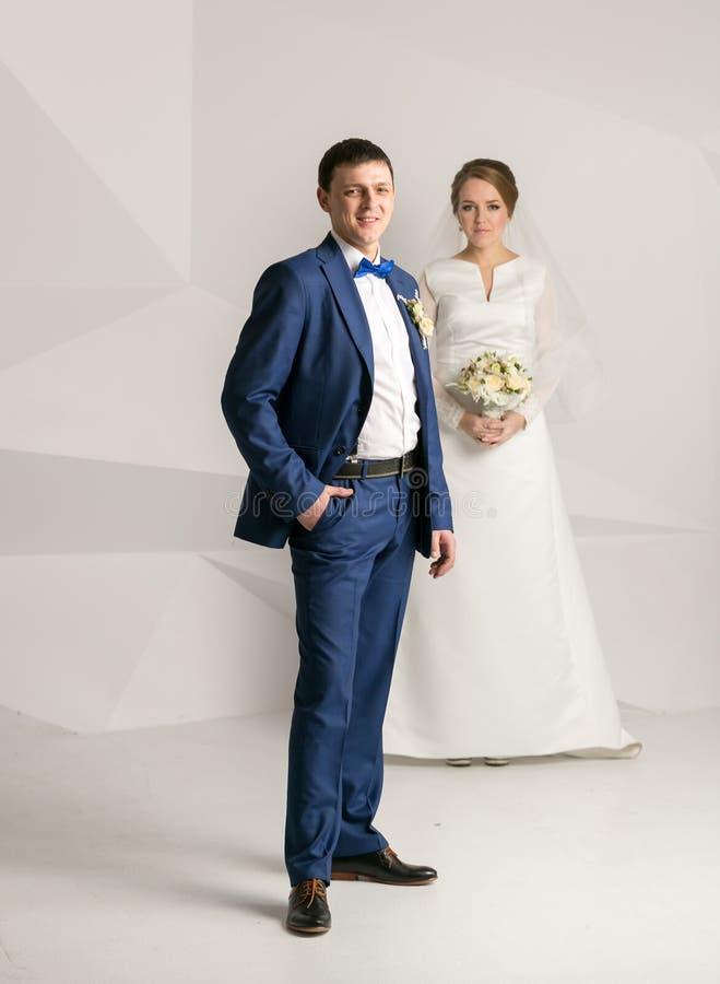 Ευτυχής νεόνυμφος στην τοποθέτηση κοστουμιών στο στούντιο με τη νύφη στοκ εικόνες