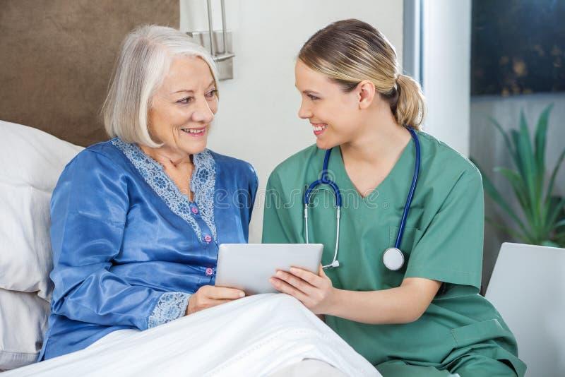 Ευτυχής νοσοκόμα και ανώτερη γυναίκα που χρησιμοποιούν το PC ταμπλετών στοκ εικόνα