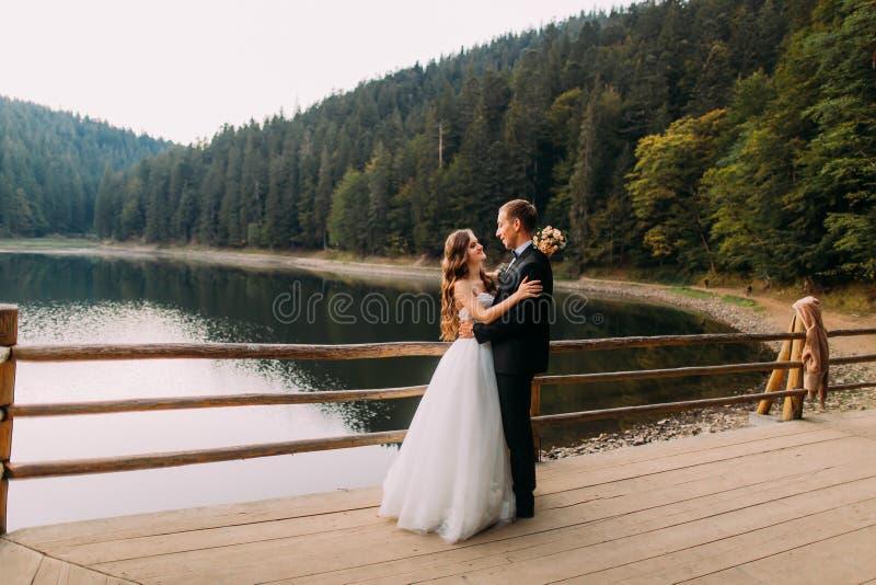 Ευτυχής νύφη γαμήλιων ζευγών πολυτέλειας με την ανθοδέσμη και νεόνυμφος που αγκαλιάζει κοντά στο φράκτη στο υπόβαθρο λιμνών κάτω  στοκ εικόνες
