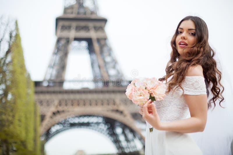 Ευτυχής νύφη με την ανθοδέσμη των λουλουδιών που θέτουν σε έναν πύργο του Άιφελ υποβάθρου ηλιοβασιλέματος στοκ εικόνες