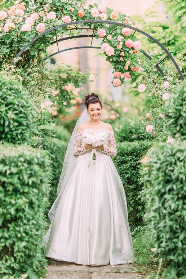 Ευτυχής νύφη με τη γαμήλια ανθοδέσμη στο υπόβαθρο της αψίδας των ρόδινων τριαντάφυλλων στοκ εικόνα με δικαίωμα ελεύθερης χρήσης