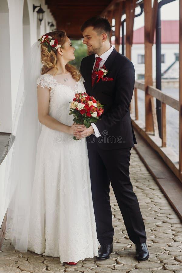 Ευτυχής νύφη που αγκαλιάζει με το νεόνυμφο, όμορφη νύφη blone στο άσπρο W στοκ εικόνα με δικαίωμα ελεύθερης χρήσης