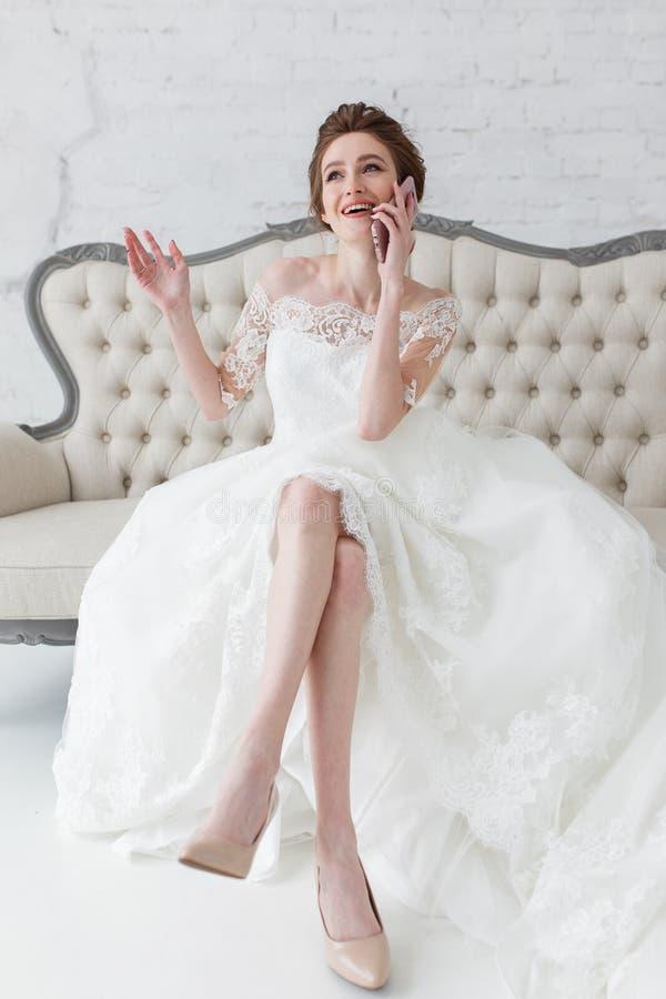 Ευτυχής νύφη που μιλά πέρα από την τηλεφωνική συνεδρίαση κυττάρων στον κλασικό καναπέ πολυτέλειας στοκ φωτογραφία με δικαίωμα ελεύθερης χρήσης