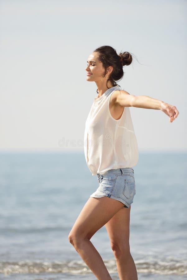 Ευτυχής ξένοιαστη γυναίκα που απολαμβάνει το όμορφο ηλιοβασίλεμα στην παραλία στοκ εικόνα με δικαίωμα ελεύθερης χρήσης