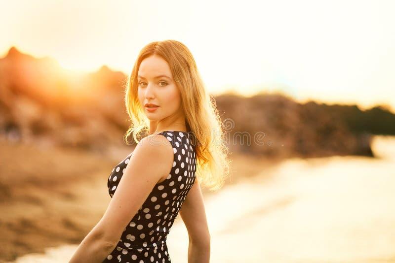 Ευτυχής ξένοιαστη γυναίκα που απολαμβάνει το όμορφο ηλιοβασίλεμα στην παραλία στοκ εικόνες