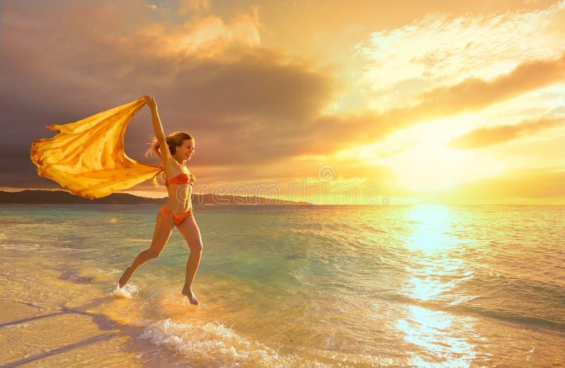 Ευτυχής ξένοιαστη γυναίκα που τρέχει στο ηλιοβασίλεμα στην παραλία στοκ φωτογραφίες