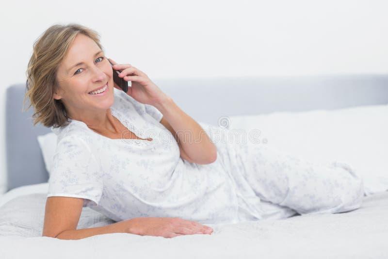 Ευτυχής ξανθή γυναίκα που βρίσκεται στο κρεβάτι που κάνει ένα τηλεφώνημα στοκ εικόνες