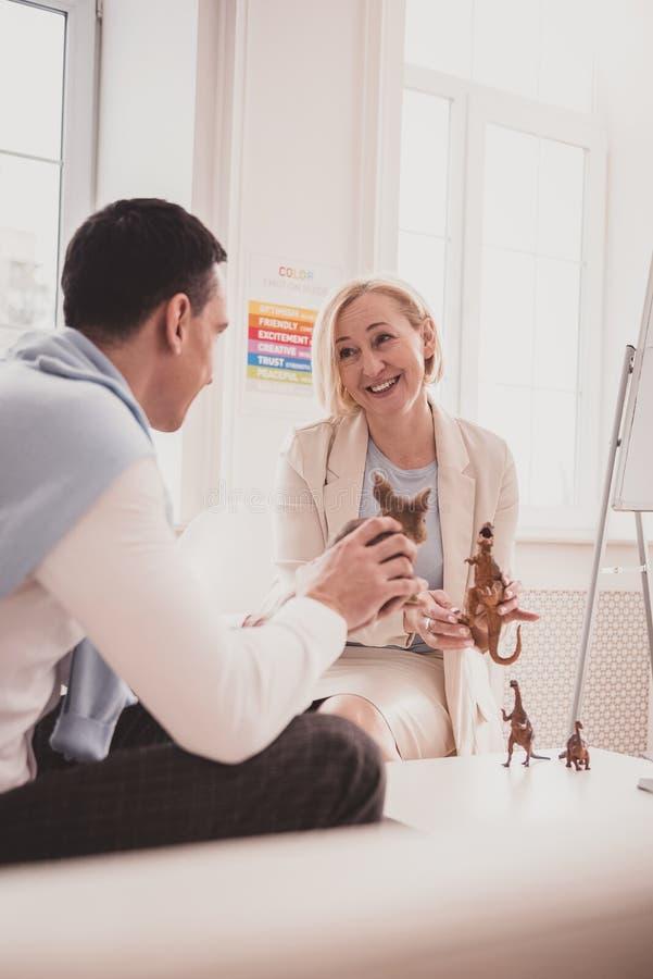Ευτυχής ξανθή γυναίκα που διοργανώνει τη φιλική συζήτηση με τον ασθενή στοκ εικόνες