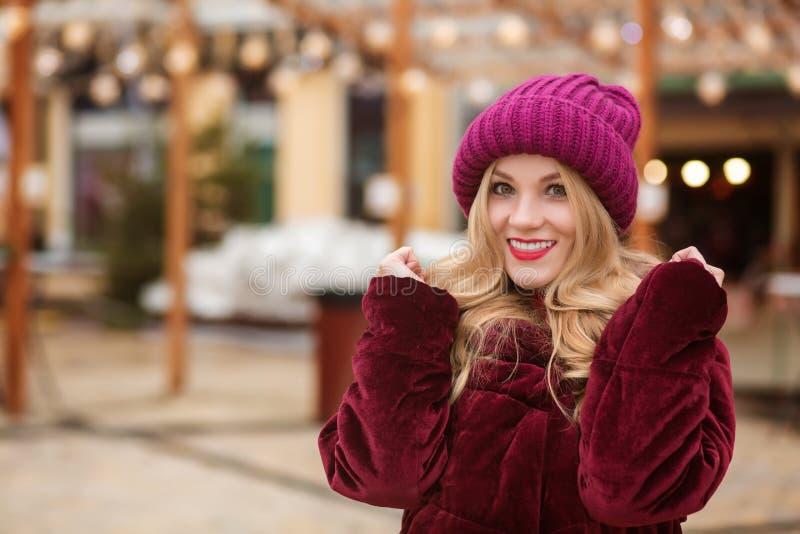 Ευτυχής ξανθή γυναίκα που φορά τα θερμά χειμερινά ενδύματα, που θέτουν στο BA στοκ φωτογραφίες με δικαίωμα ελεύθερης χρήσης