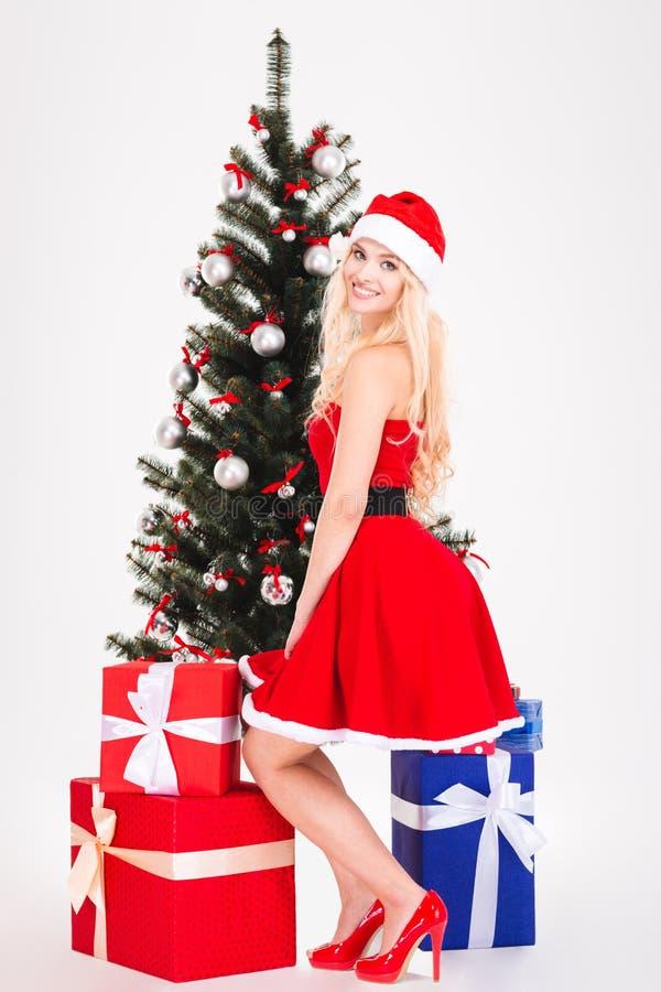 Ευτυχής ξανθή γυναίκα στην τοποθέτηση υφασμάτων santa κοντά στο χριστουγεννιάτικο δέντρο στοκ φωτογραφία