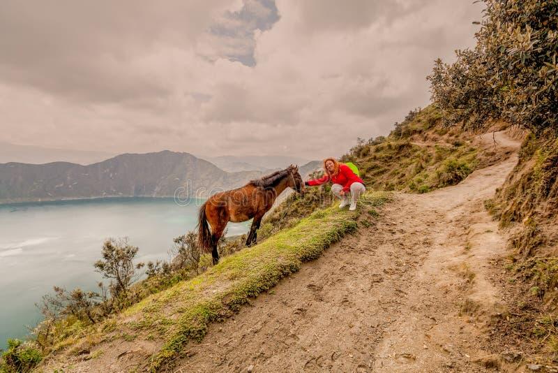 Ευτυχής ξανθή συνεδρίαση γυναικών στην άκρη του βουνού στοκ εικόνα