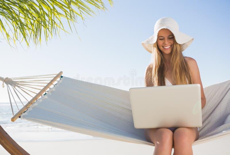 Ευτυχής ξανθή συνεδρίαση στην αιώρα που χρησιμοποιεί το lap-top στοκ εικόνα με δικαίωμα ελεύθερης χρήσης