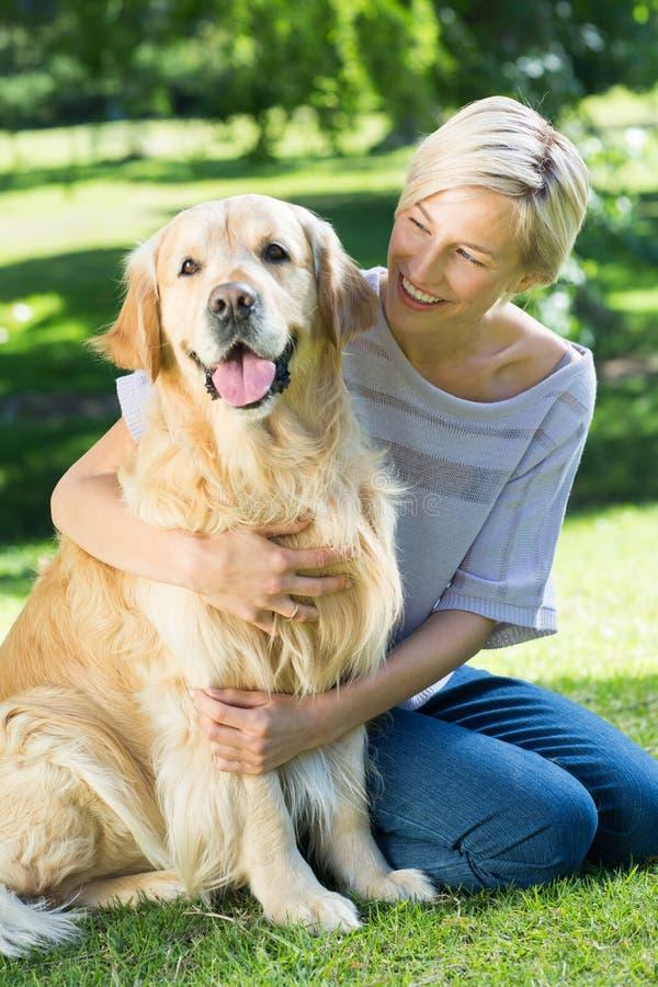 Ευτυχής ξανθός αγκαλιάζοντας το σκυλί της στο πάρκο στοκ φωτογραφίες