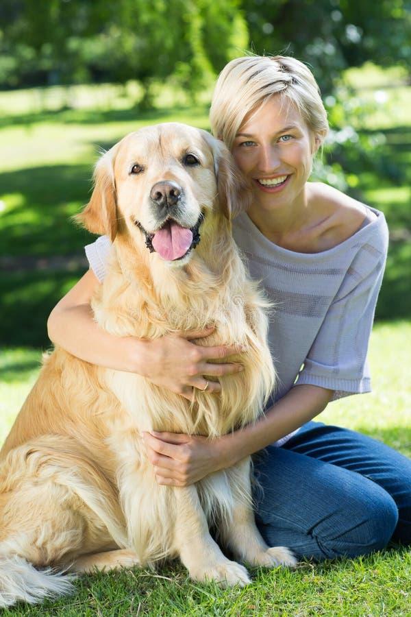 Ευτυχής ξανθός αγκαλιάζοντας το σκυλί της στο πάρκο στοκ φωτογραφία με δικαίωμα ελεύθερης χρήσης
