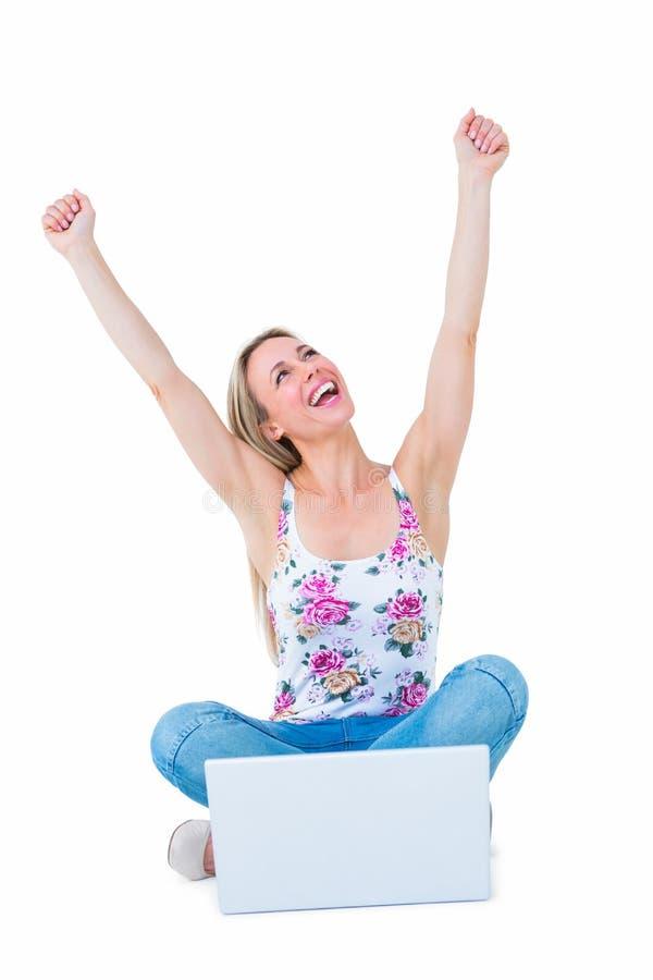 Ευτυχής ξανθός ενθαρρυντικός με τα όπλα επάνω κοντά στο lap-top της στοκ φωτογραφία