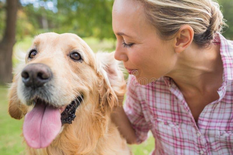 Ευτυχής ξανθός με το σκυλί της στο πάρκο στοκ εικόνα με δικαίωμα ελεύθερης χρήσης