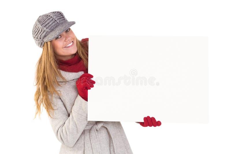 Ευτυχής ξανθός στα χειμερινά ενδύματα που παρουσιάζουν κάρτα στοκ εικόνες με δικαίωμα ελεύθερης χρήσης