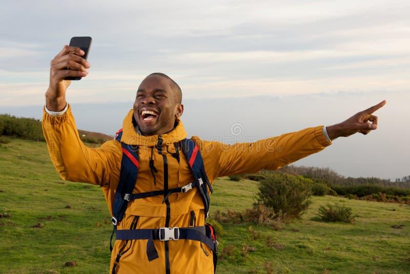Ευτυχής οδοιπόρος αφροαμερικάνων που παίρνει selfie και που δείχνει στην άποψη στοκ εικόνες