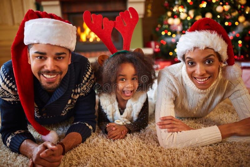 Ευτυχής οικογένεια αφροαμερικάνων με τα καπέλα Santa στοκ εικόνα